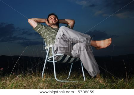 Young Muslim Man Is Sitting On Meadow, Sunset Time
