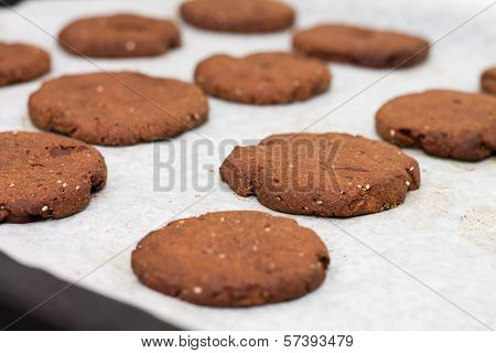 Tray of chocolate cacao chia seed cookies stacked on white parchment paper close-up