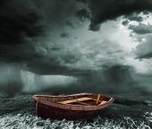 stock photo of old boat  - an old boat in the stormy ocean - JPG
