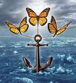 stock photo of monarch  - Lifting the burden business concept as a group of three monarch butterflies raising a heavy nautical anchor from a stormy ocean scene as a metaphor for liberation and unstopable freedom by working together as a team - JPG
