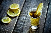 stock photo of liquor bottle  - tequila and lemon on a wood background - JPG