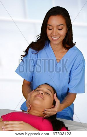 Female chiropractor working at her office with a patient