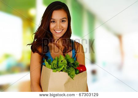 Woman smiling with a bag of groceries
