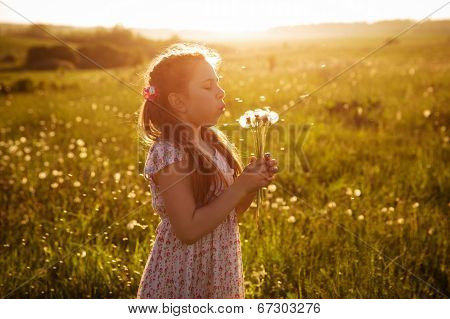 Girl Blowing A Bouquet Of Dandelions