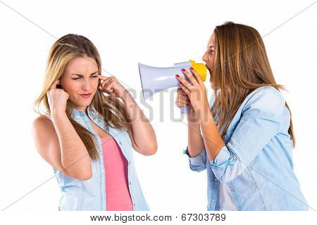 Girl Shouting With A Megaphone At Her Friend