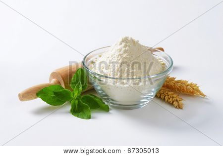 glass bowl with soft wheat flour, rolling pin and wheat ear