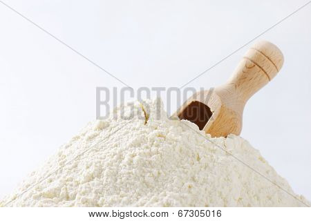heap of all-purpose flour with immersed measuring spoon