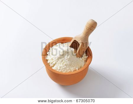 measured portion of flour in the ceramic bowl with immersed measuring spoon