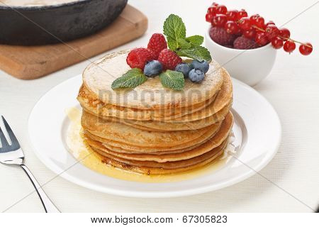 Pile Of Delicious Handmade Pancakes Topped With Raspberries And Bilberries On Feast Table