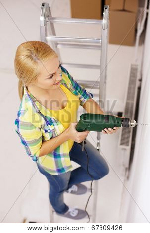 repair, building and home concept - smiling woman with electric drill making hole in wall