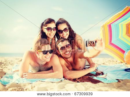 summer, holidays, vacation, technology and happiness concept - group of smiling people in sunglasses taking picture with smartphone on beach