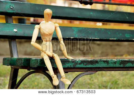 Wooden pose puppet sitting on bench outdoors