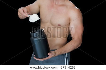 Muscular man scooping up protein powder on black background