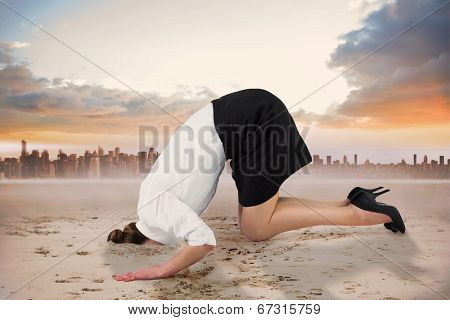 Businesswoman burying her head against cityscape on the horizon
