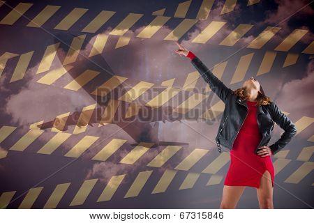Composite image of brunette in red dress and biker jacket against warning tape