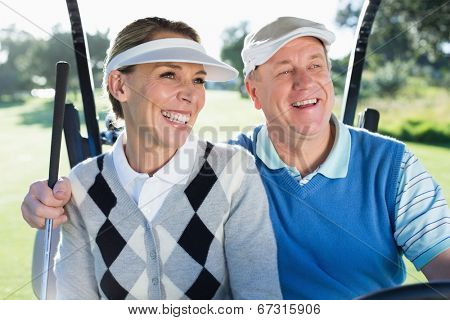 Happy golfing couple sitting in golf buggy smiling on a sunny day at the golf course