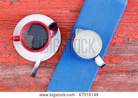 Cup Of Black Coffee On A Rustic Red Picnic Table