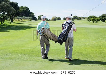 Golfer friends walking holding their golf bags on a sunny day at the golf course