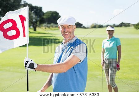 Happy golfer holding eighteenth hole flag with partner behind him on a sunny day at the golf course