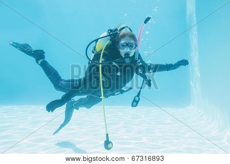 Woman on scuba training submerged in swimming pool on her holidays