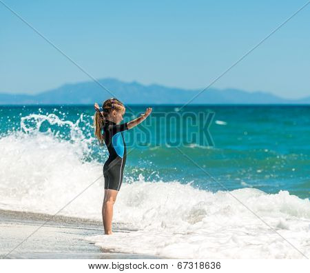 happy little girl playing in a wetsuit on the beach