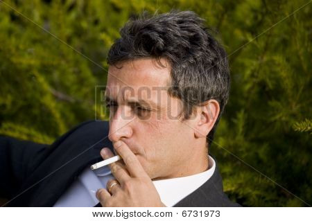 handsome white man smoking a sigarette outdoor in a sunny day