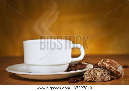 White Cup Of Hot Coffee On A Saucer And Two Cakes