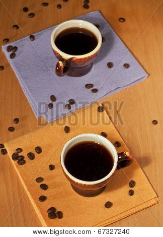 Two Cups Of Coffee On Napkins With Coffee Beans