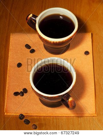 Two Cups Of Coffee On A Yellow Napkin