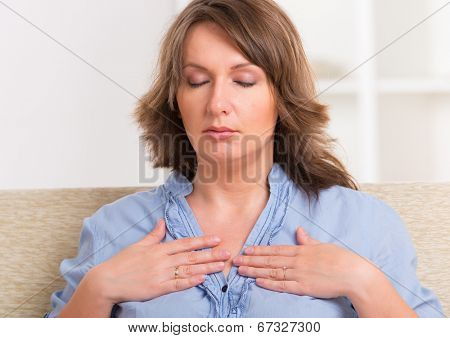 Woman practicing self Reiki transfering energy through palms, a kind of energy medicine.