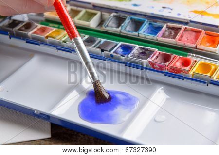 Professional watercolor aquarell paints in box with brush in water