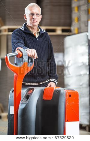 A man who works in a distribution centre is posing next to a pallet truck in a warehouse.