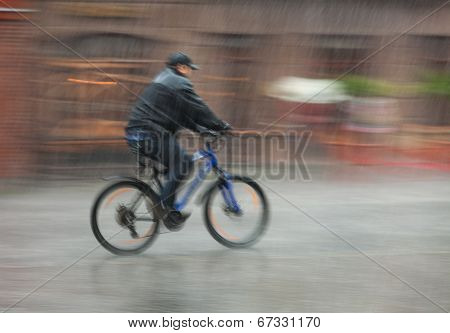 Cyclist Rides Through The Streets On A Rainy Day