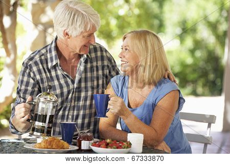 Senior couple eating breakfast outdoors