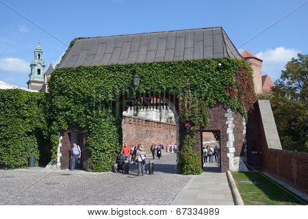 KRAKOW, POLAND - SEPTEMBER 15, 2013: Tourists under the Bernardine Gate of Wawel royal castle. Built in the XVI century, now the castle is the museum and the main attraction of the city