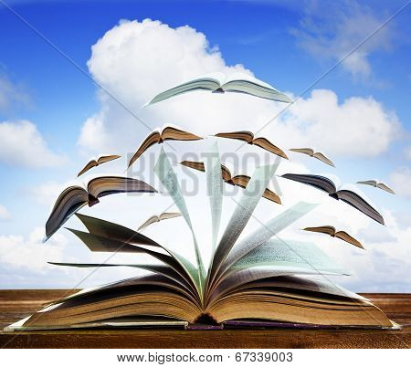 Open Old Book Page On Wood Table With Flying Book Page Against Beautiful Blue Sky Use For Abstract E