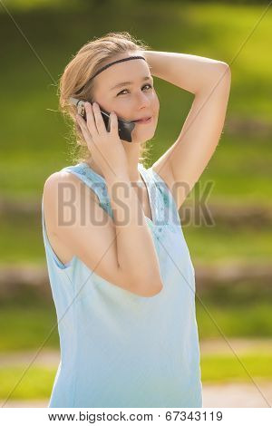 Charming Young Blond Woman Close-up Portrait In Blue Dress Speaking On Cellphone Against Green Lawn