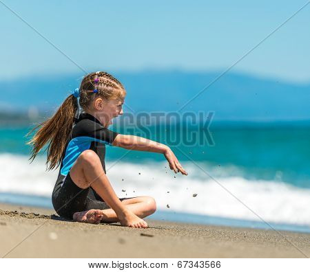 happy cute little girl sitting in a wetsuit on the beach
