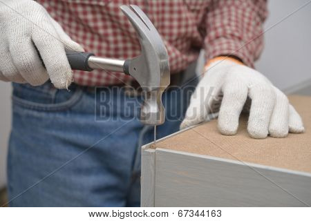 Man assembling the wooden chest. Selective focus on the nail