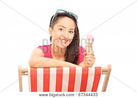 Woman eating ice cream seated on a sun longer isolated on white background