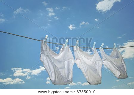 Men underwear hanging on clothesline against blue sky
