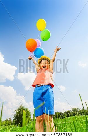 Happy girl with balloons wearing flower circlet