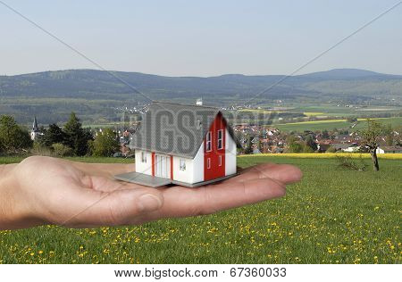 Hand With House In Front Of Landscape