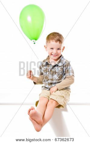 Beautiful  smiling boy sitting with balloon