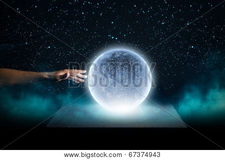 Close up of human hand touching blue glowing moon