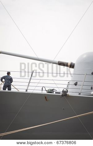 STATEN ISLAND, NY - MAY 21, 2014: A sailor on the guided-missile destroyer USS Cole (DDG 067) standing near the MK45 5 inch gun tends the lines as the ship docks at Sullivans Piers during Fleet Week NY.