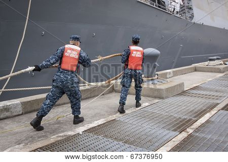 STATEN ISLAND, NY - MAY 21, 2014: Sailors from NWS Earle Port Services tend the lines of the guided-missile destroyer USS Cole (DDG 067) as the ship docks at Sullivans Piers for Fleet Week NY.
