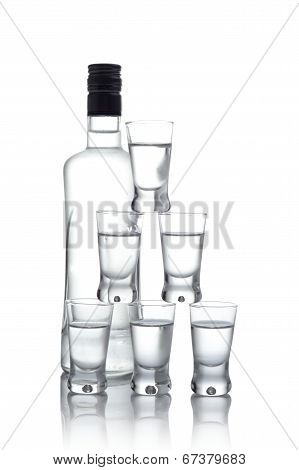 Bottle With Many Glasses Of Vodka Isolated On White Background