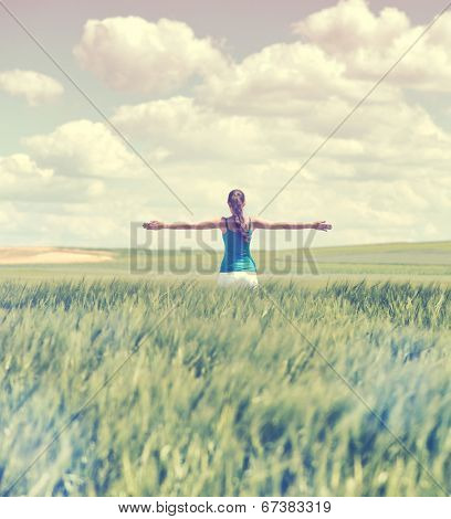 Faded retro style image of a girl in a wheat field standing in the distance with her back to the camera and her arms outspread in celebration of a beautiful sunny summer day and freedom