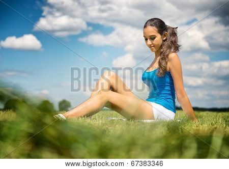 Beautiful slender tanned leggy young girl in shorts sitting relaxing in a green field in the warm summer sunshine, low angle view under a blue sky with fluffy white clouds